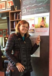 Dori Jones Yang poses by the poster announcing her November 2016 author talk in Beijing